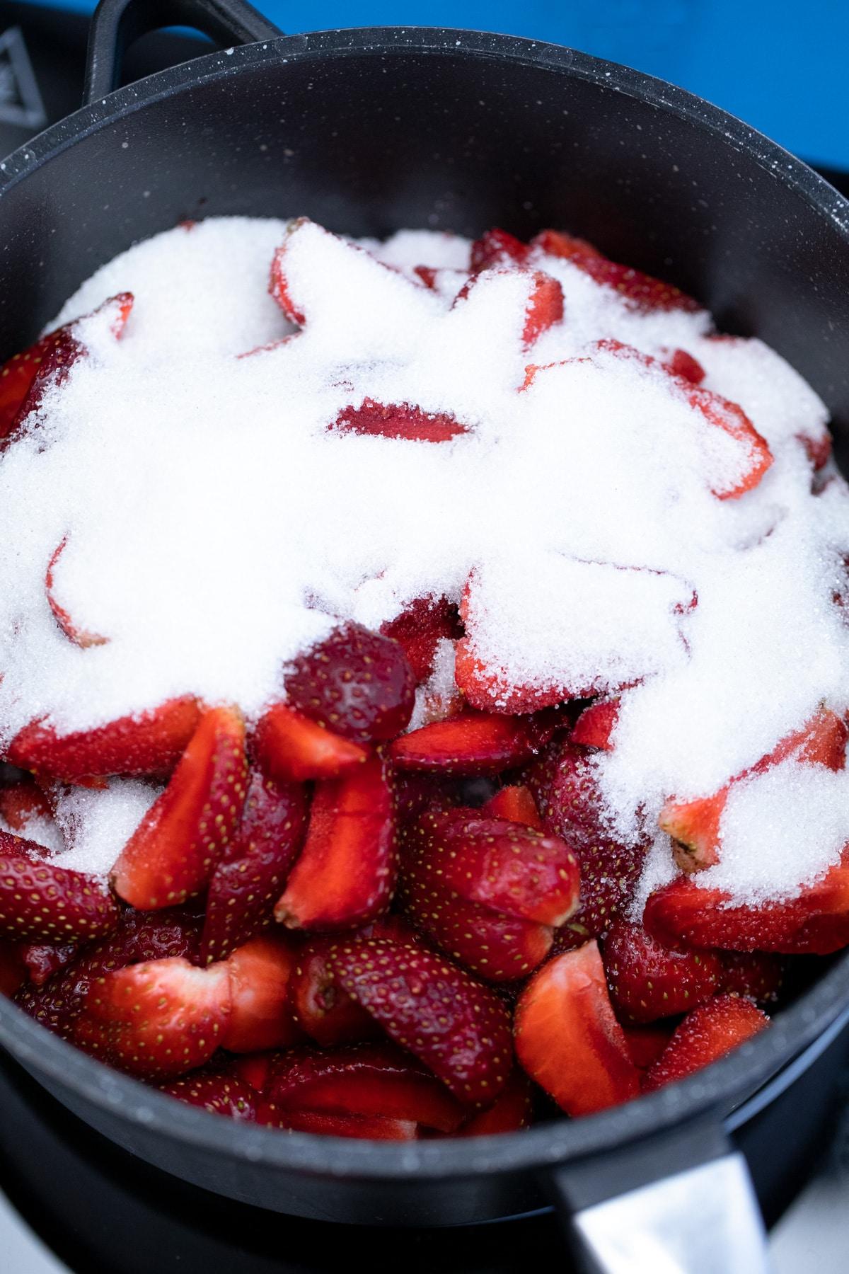 Sugar coating strawberries in large pot