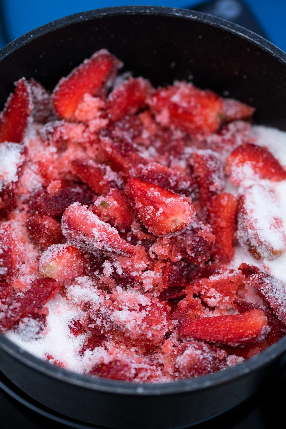 Strawberries coated in sugar in large black pot