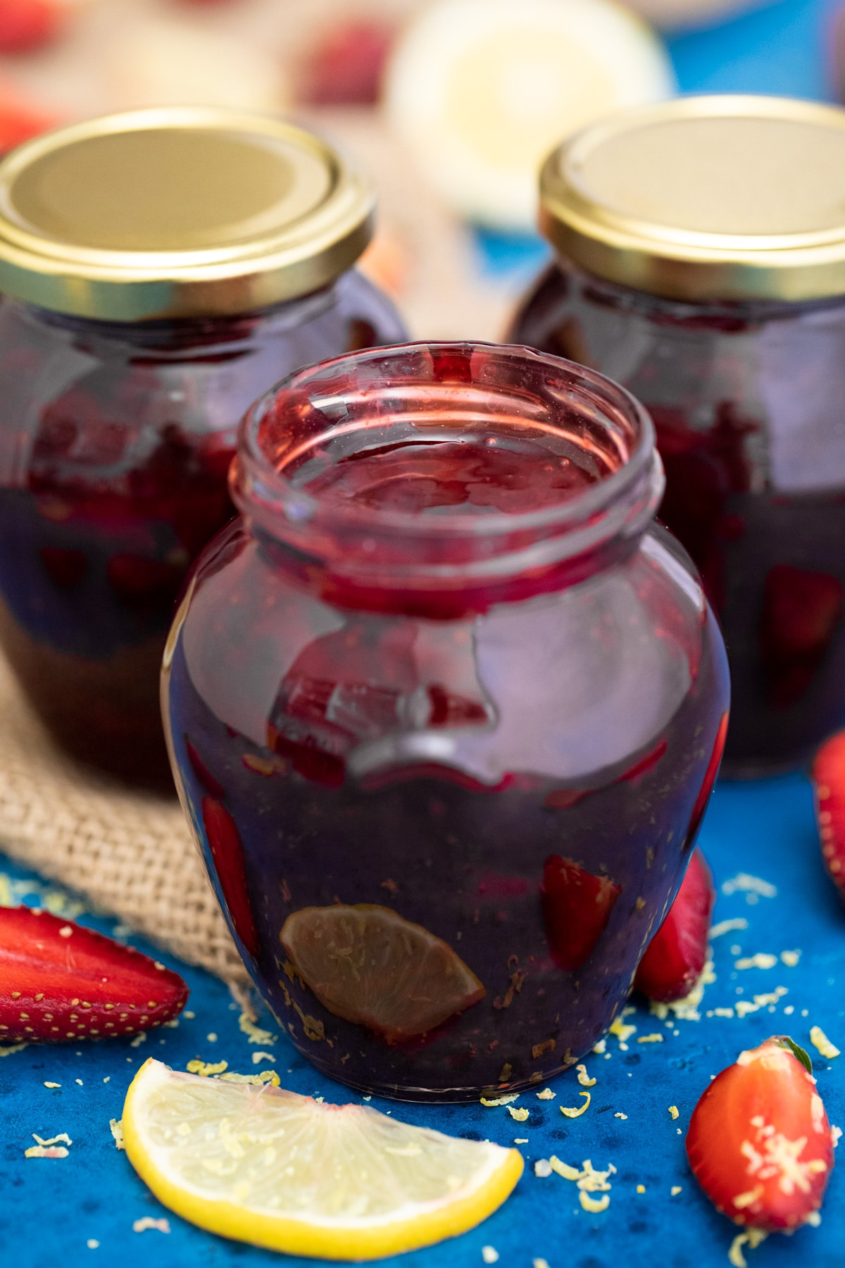 Pear shaped jars of strawberry jam on blue table with berries and lemon