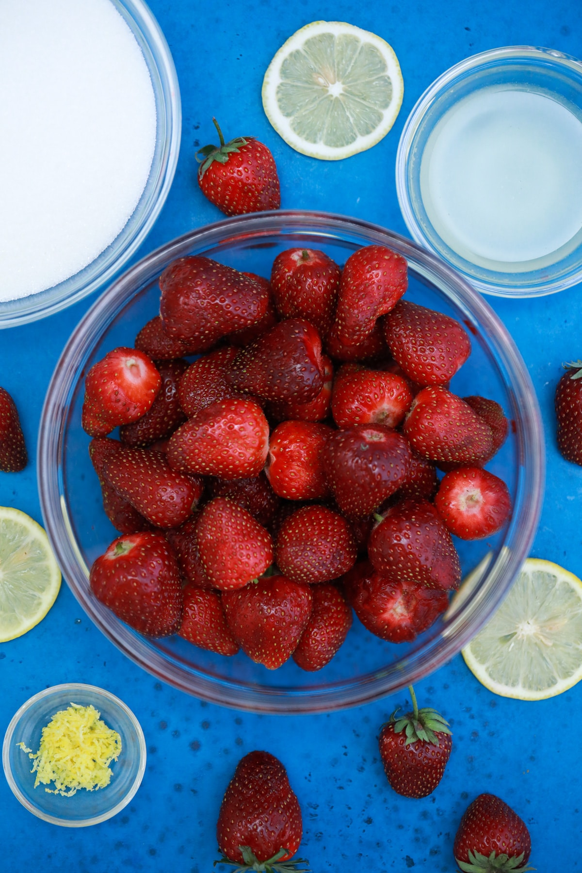 Ingredients for strawberry jam in glass bowls on blue table