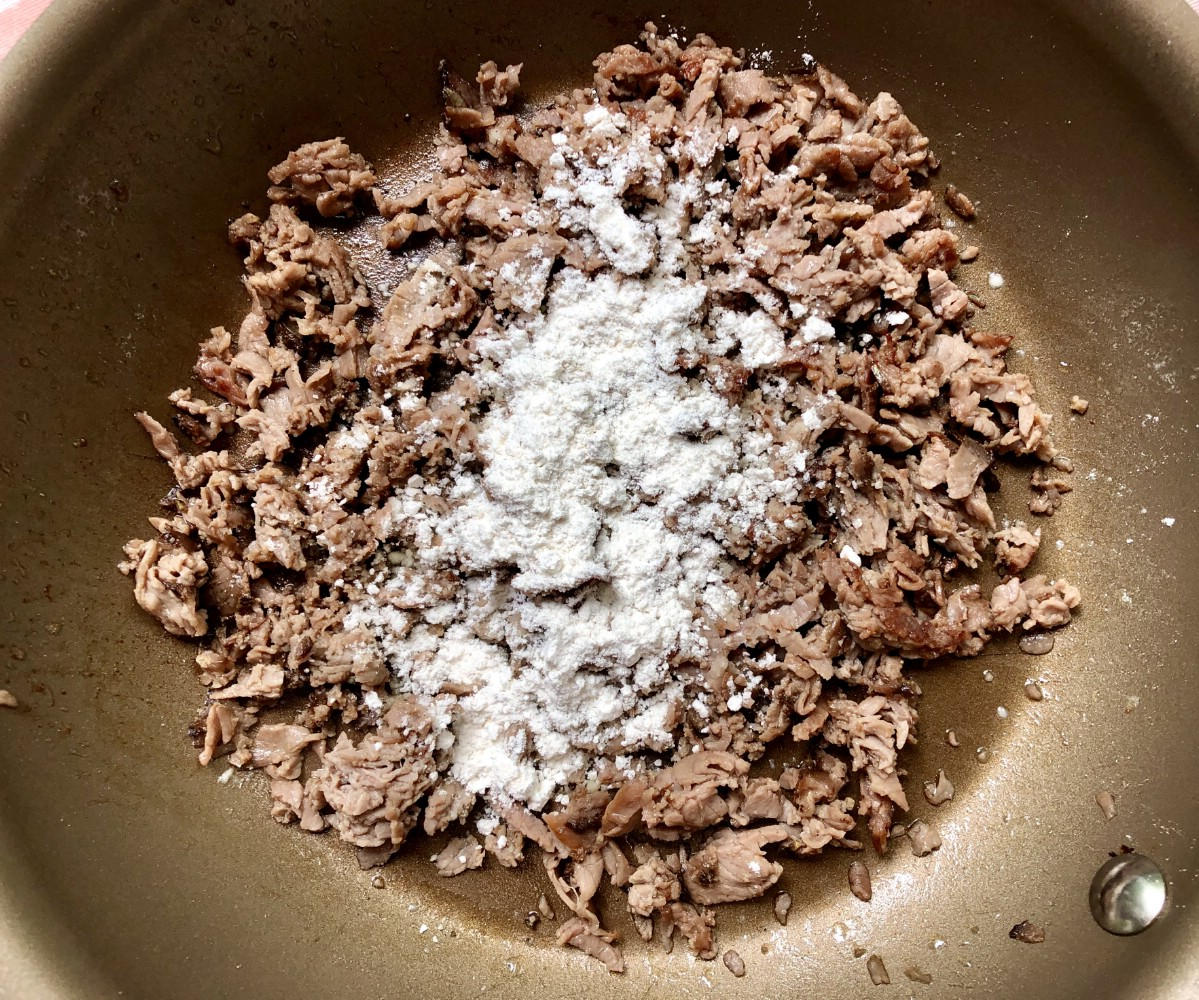 Adding flour to beef in skillet