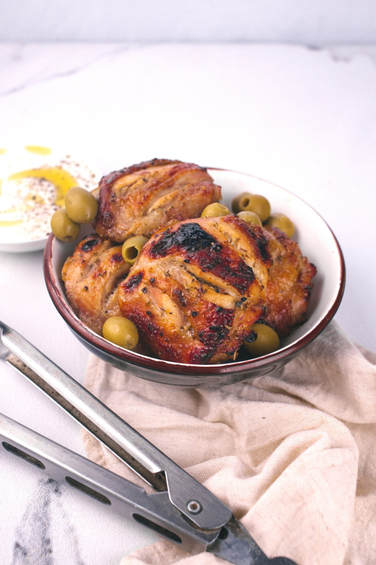 Chicken thighs in bowl with olives