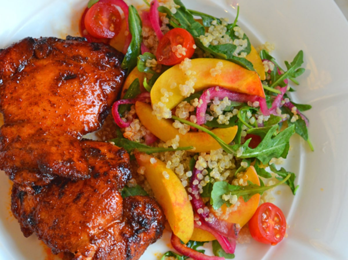 Red chicken thighs on plate with salad