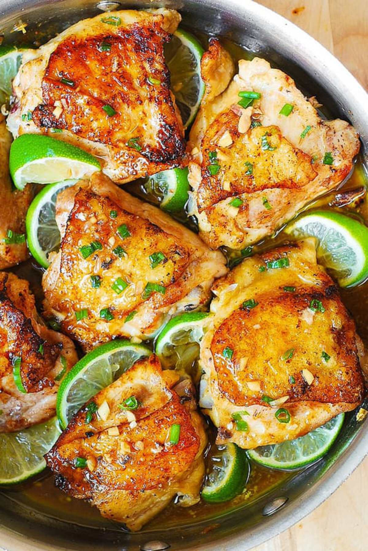 Chicken thighs with lime wedges in skillet