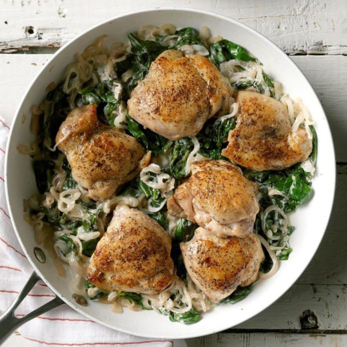 Chicken thighs on spinach in skillet