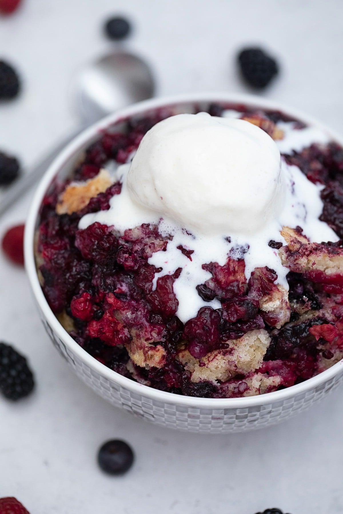 Scoop of ice cream on berry cobbler