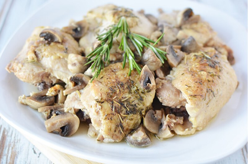 Chicken thighs on white plate with herbs