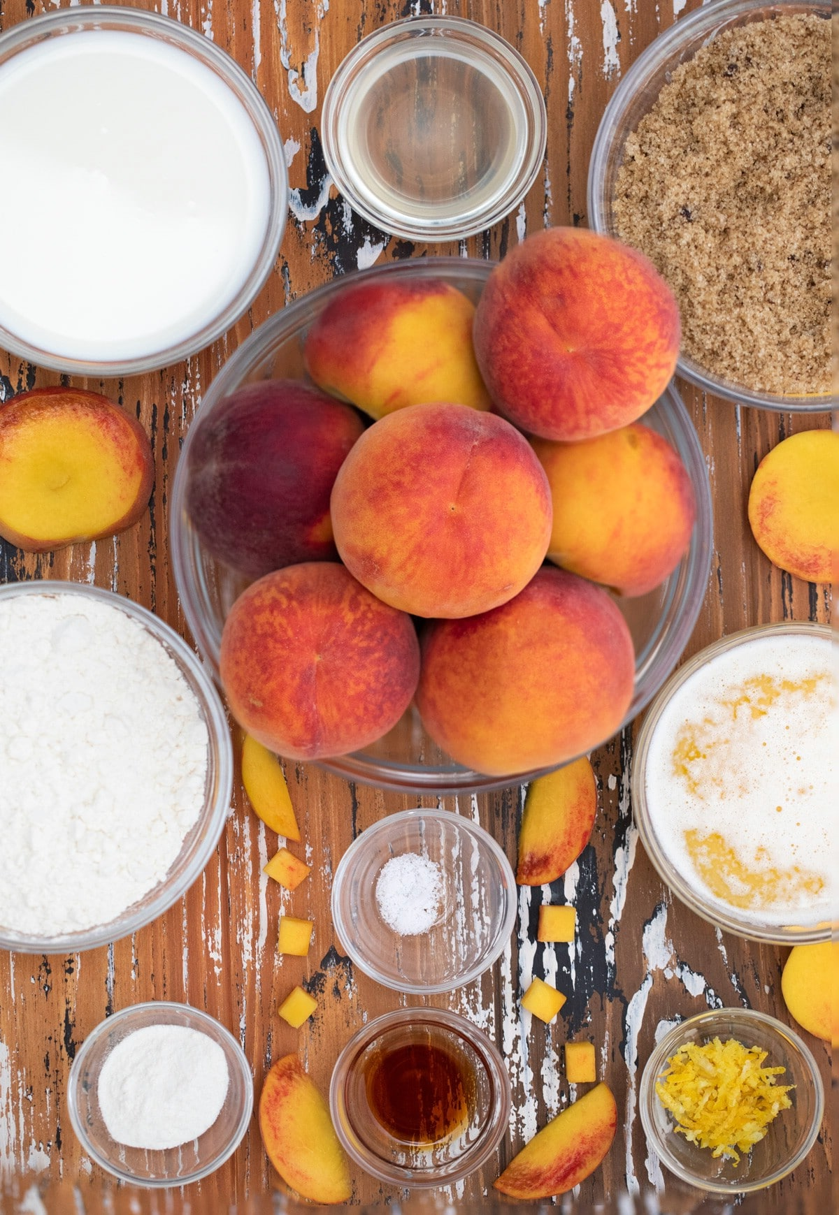 Ingredients in glass bowls for peach cobbler sitting on table