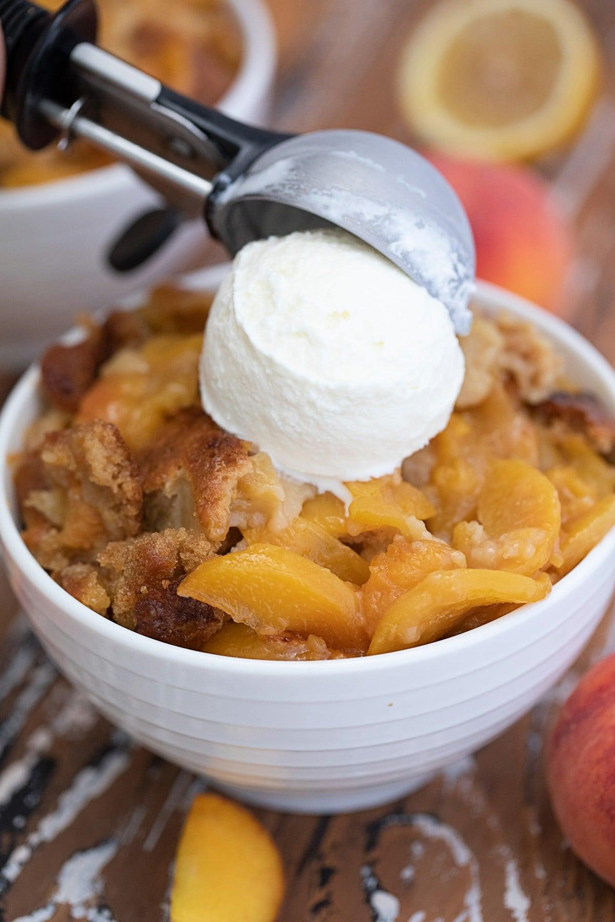 Adding ice cream to peach cobbler in white bowl