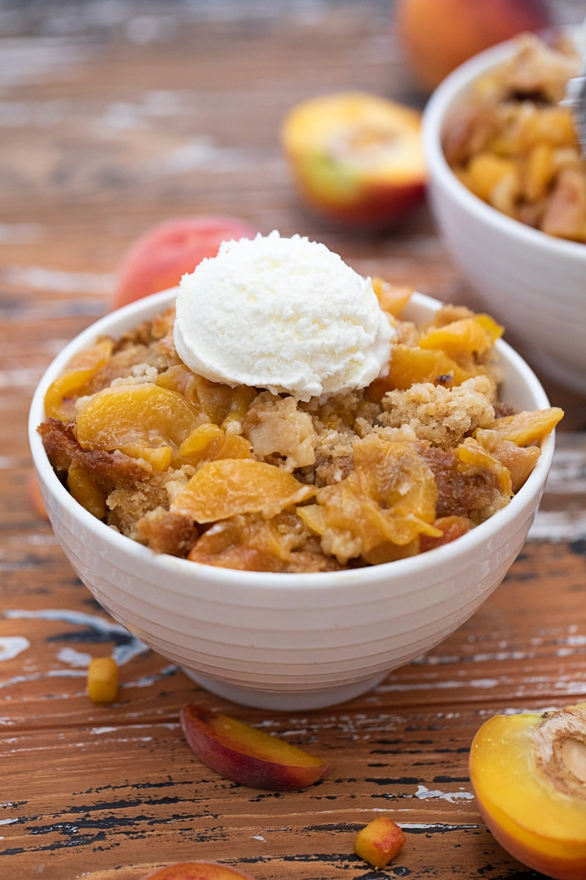 White ribbed bowl on wood table with peach cobbler and ice cream