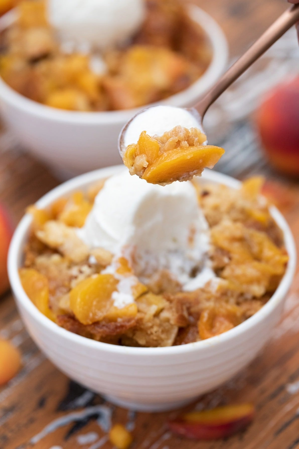 Spoon of cobbler with ice cream hovering above a bowl of cobbler on table