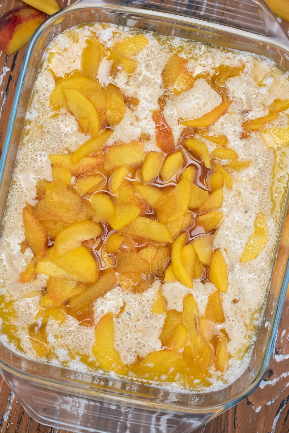 Peach cobbler before baking in large glass casserole dish
