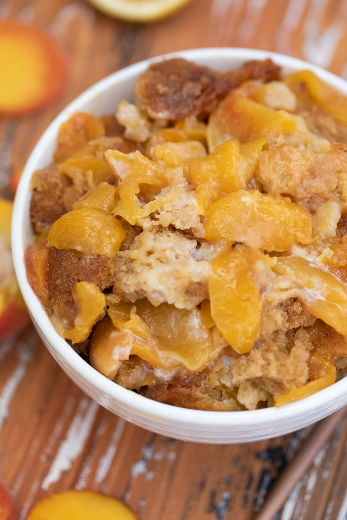White bowl of cobbler with sliced peaches