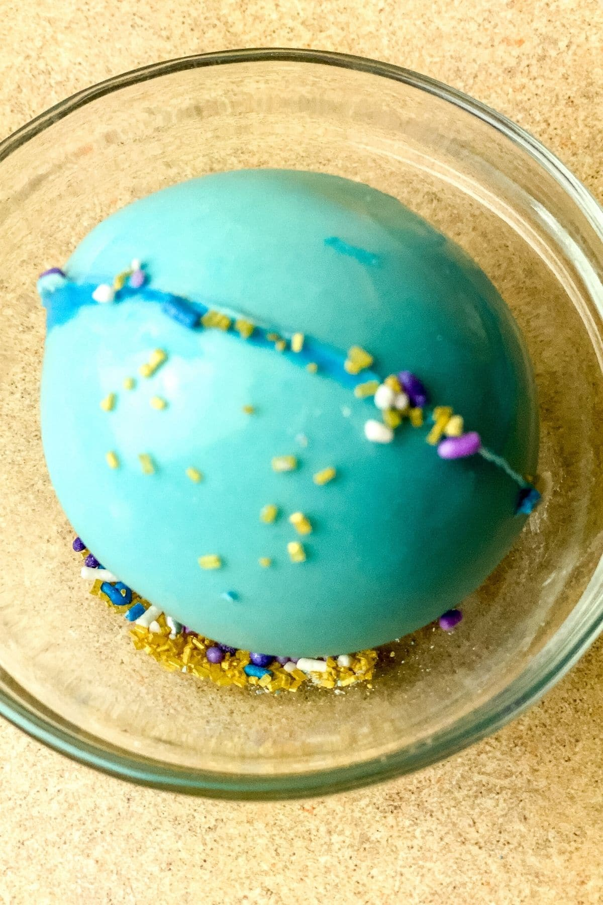 Adding sprinkles to unicorn hot cocoa bomb