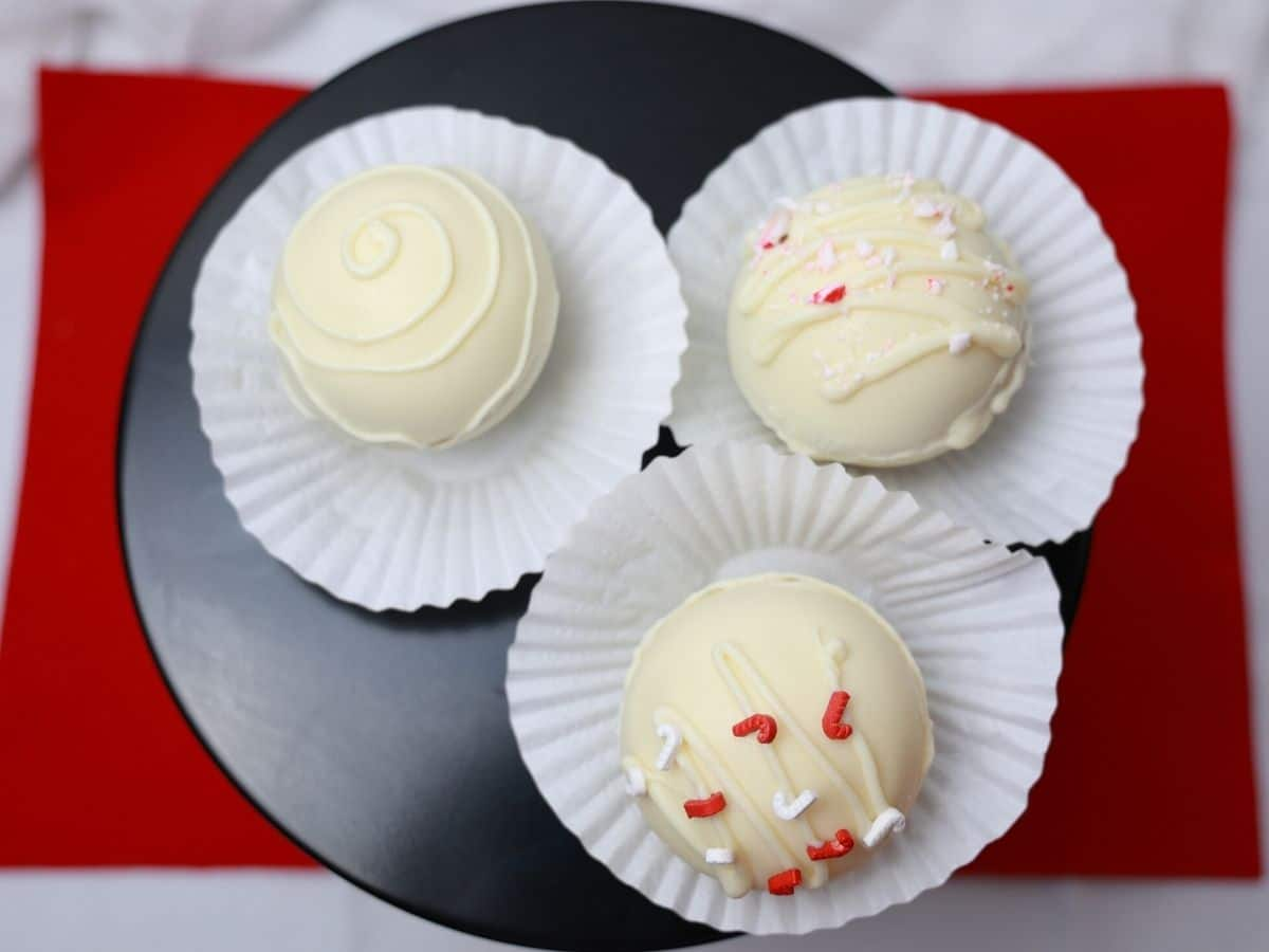White chocolate hot cocoa bombs on black platter