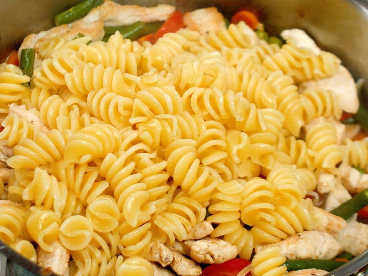 Pasta in skillet of vegetables