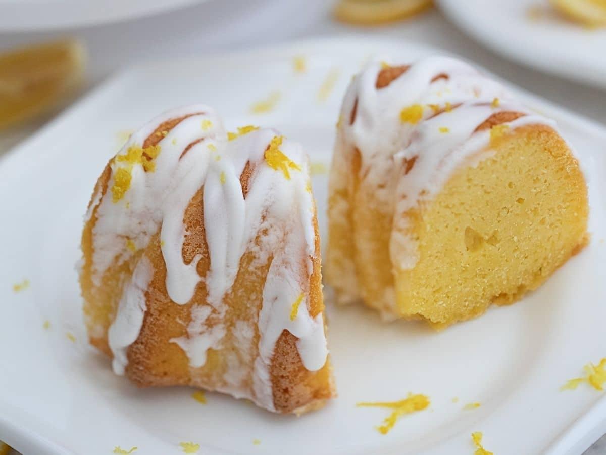Sliced lemon cake on white plate with white glaze on top