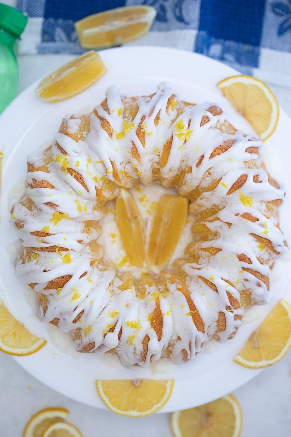 Image o bundt cake with white glaze on white plate from above