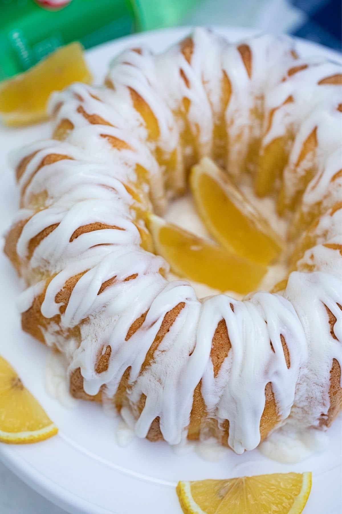 Bundt cake on white plate with glaze on top and lemon wedges on side