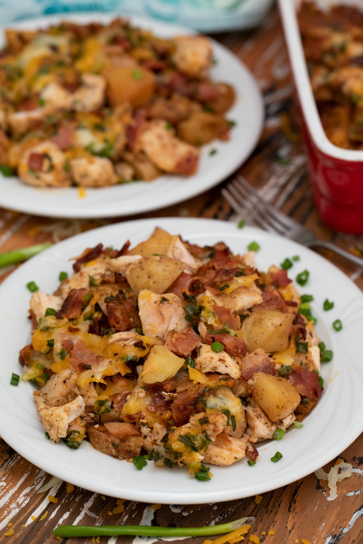White plate loaded with potato and chicken casserole with cheese and bacon