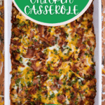 White casserole dish filled with loaded potato casserole topped with cheese and bacon