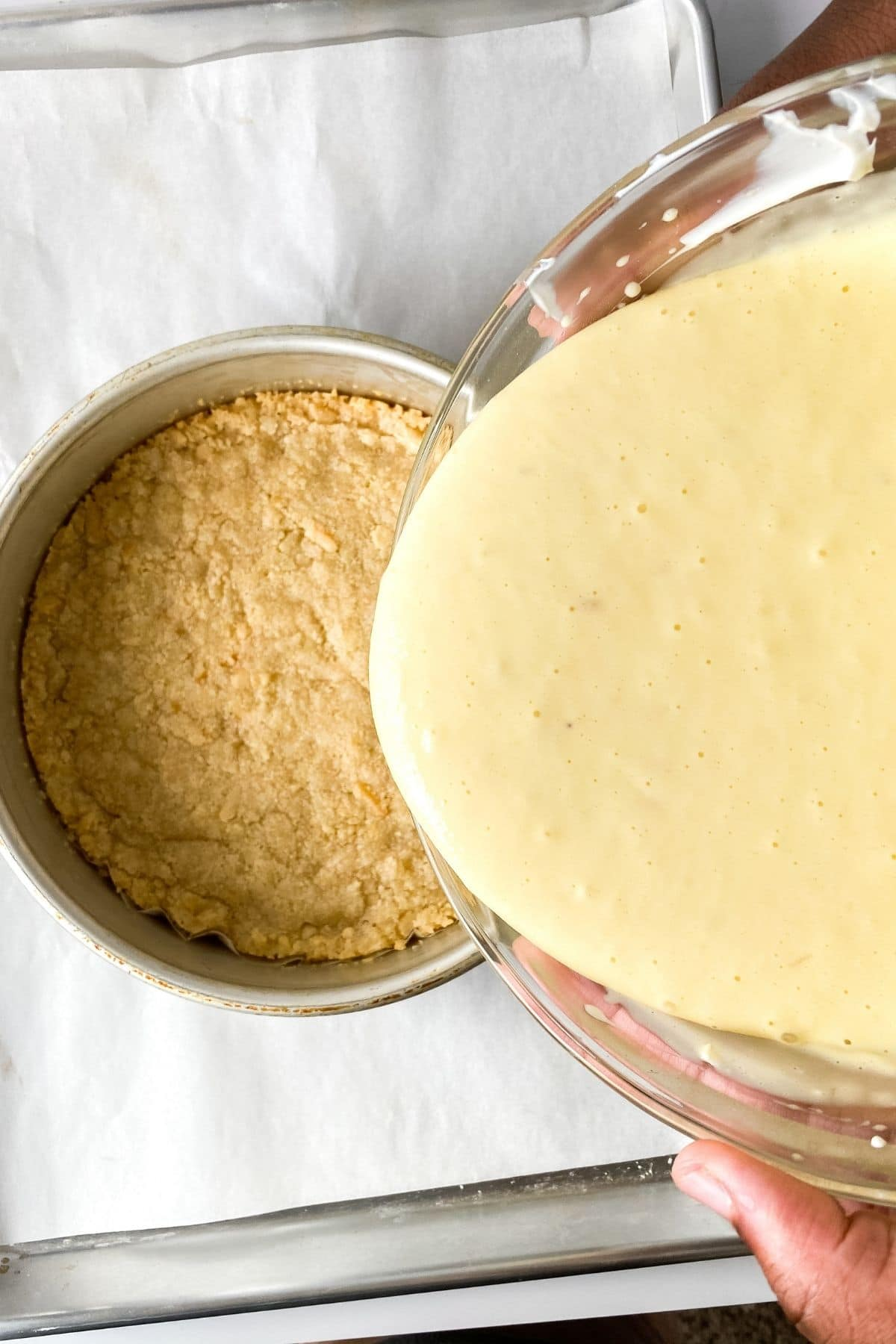 Pouring cheesecake batter in pan