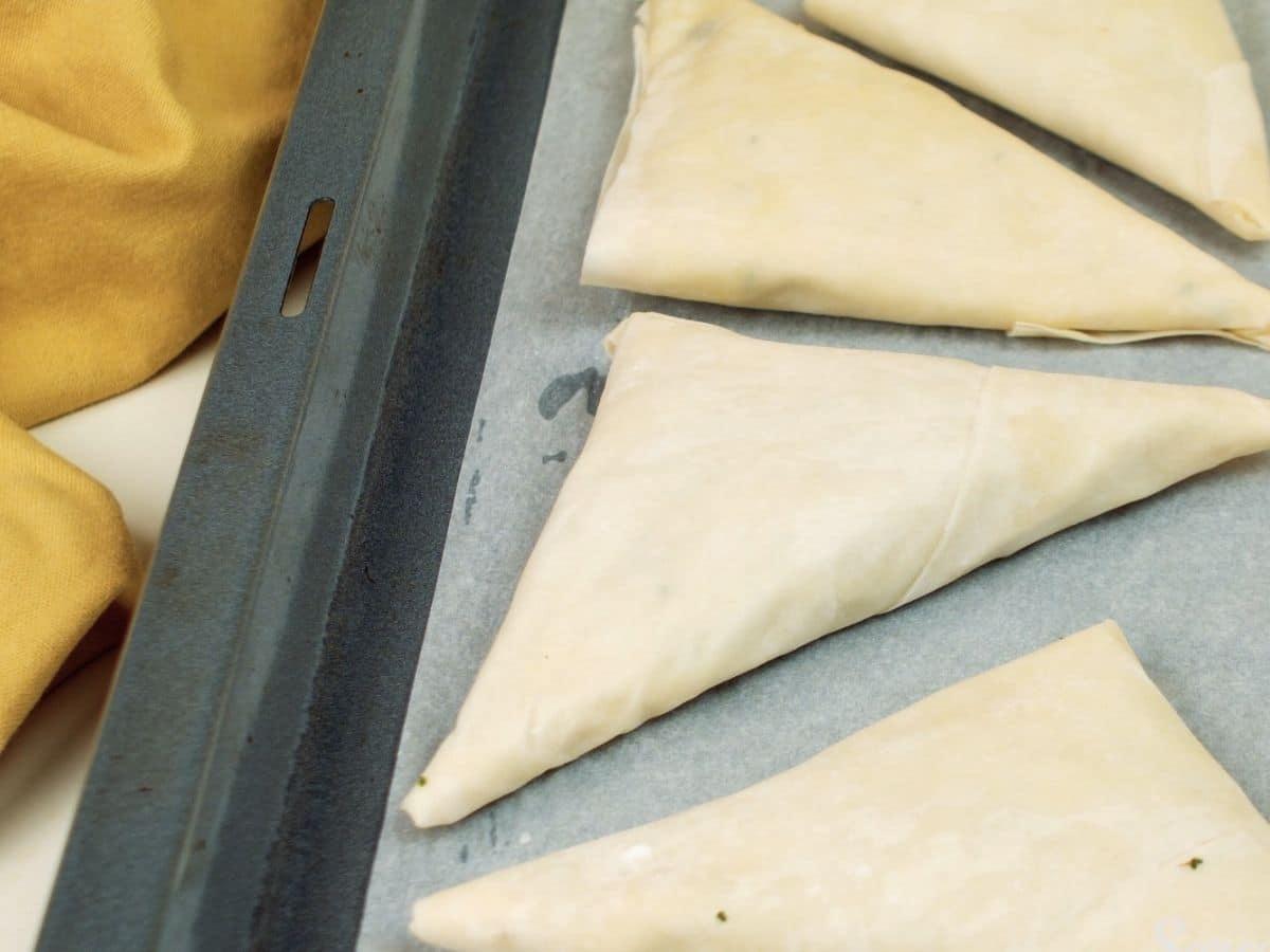Samosas on baking sheet