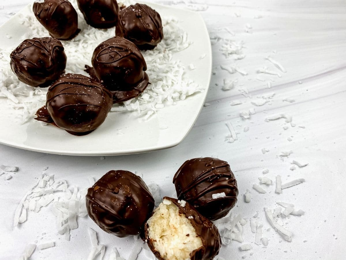 Chocolate coconut truffles on white plate