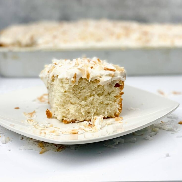 Slice of coconut cake on white plate