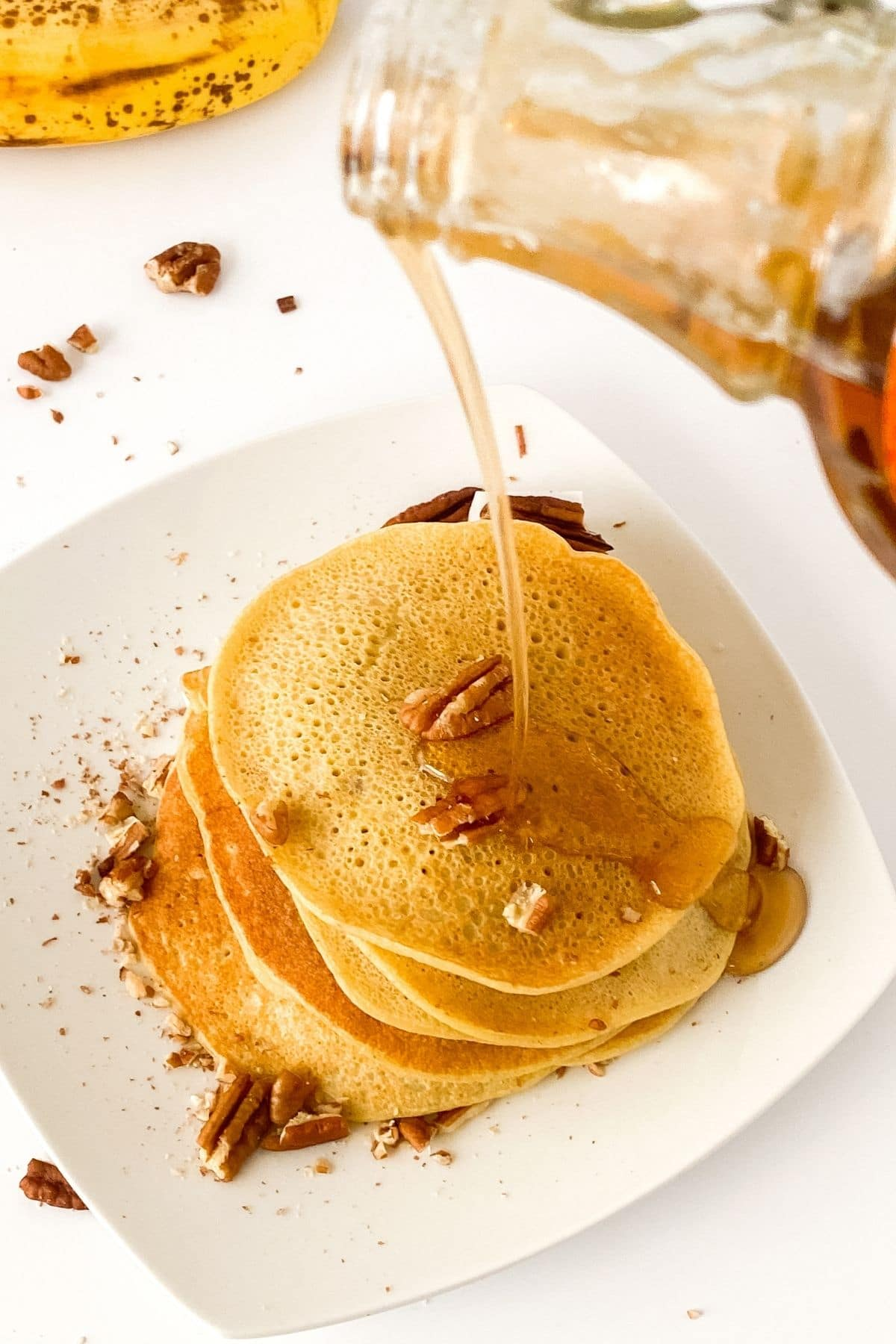 Pouring syrup onto pancakes
