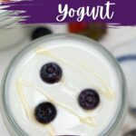 Glass jar of yogurt topped with blueberries and honey