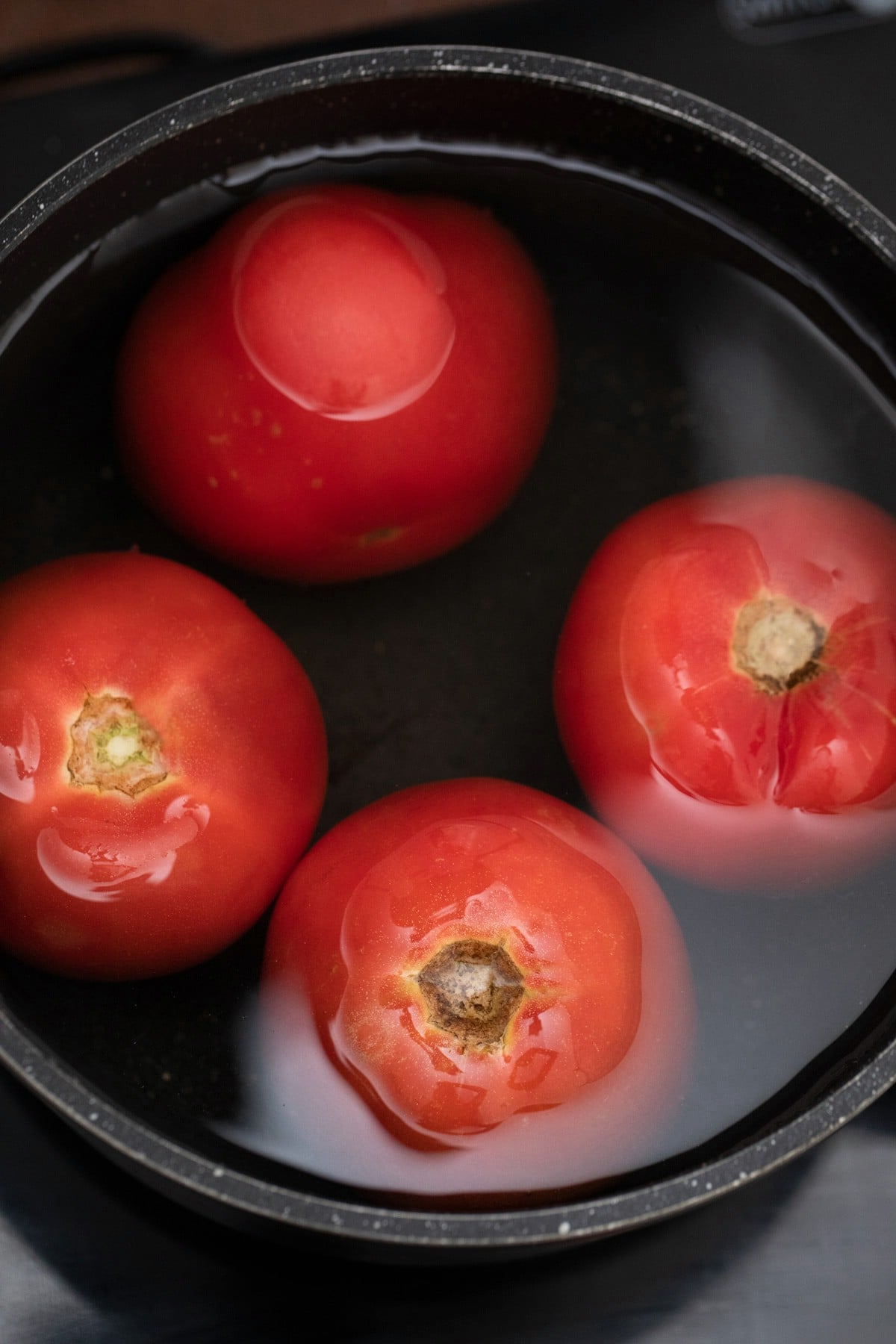 Cooking tomatoes in black stockpot