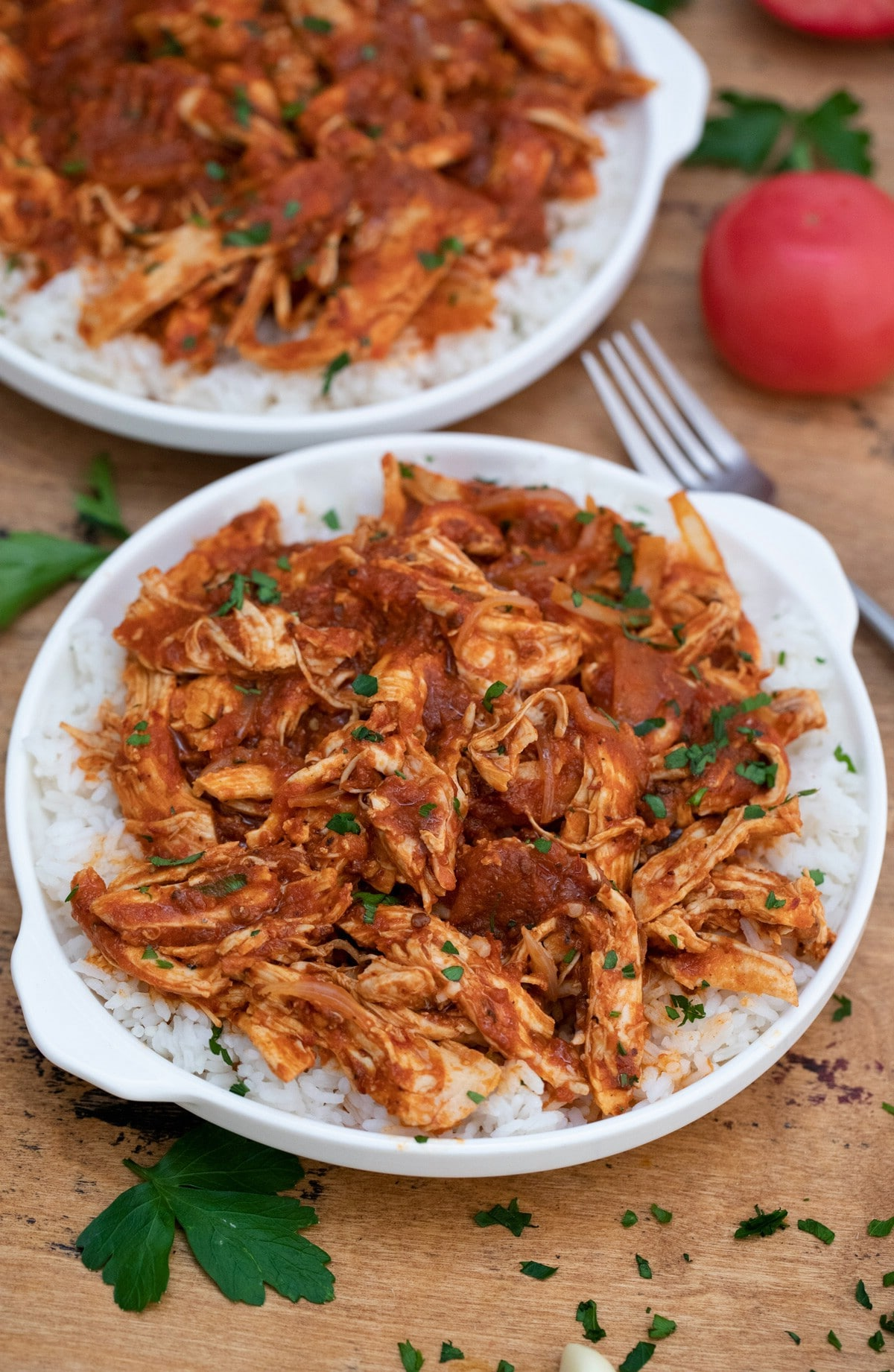 Two white plates topped with rice and Mexican chicken