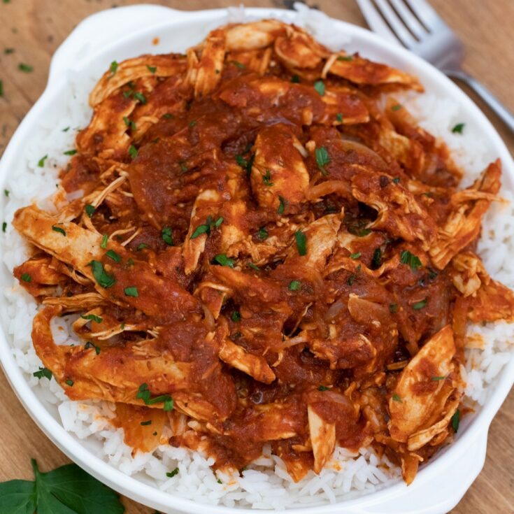Mexican chicken on a white plate with fork