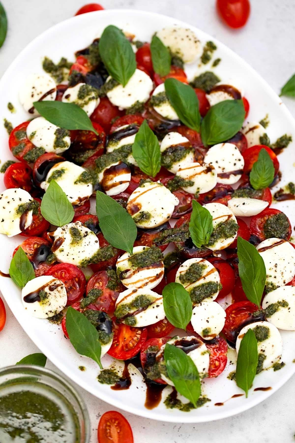 Caprese with pesto drizzle on white plate