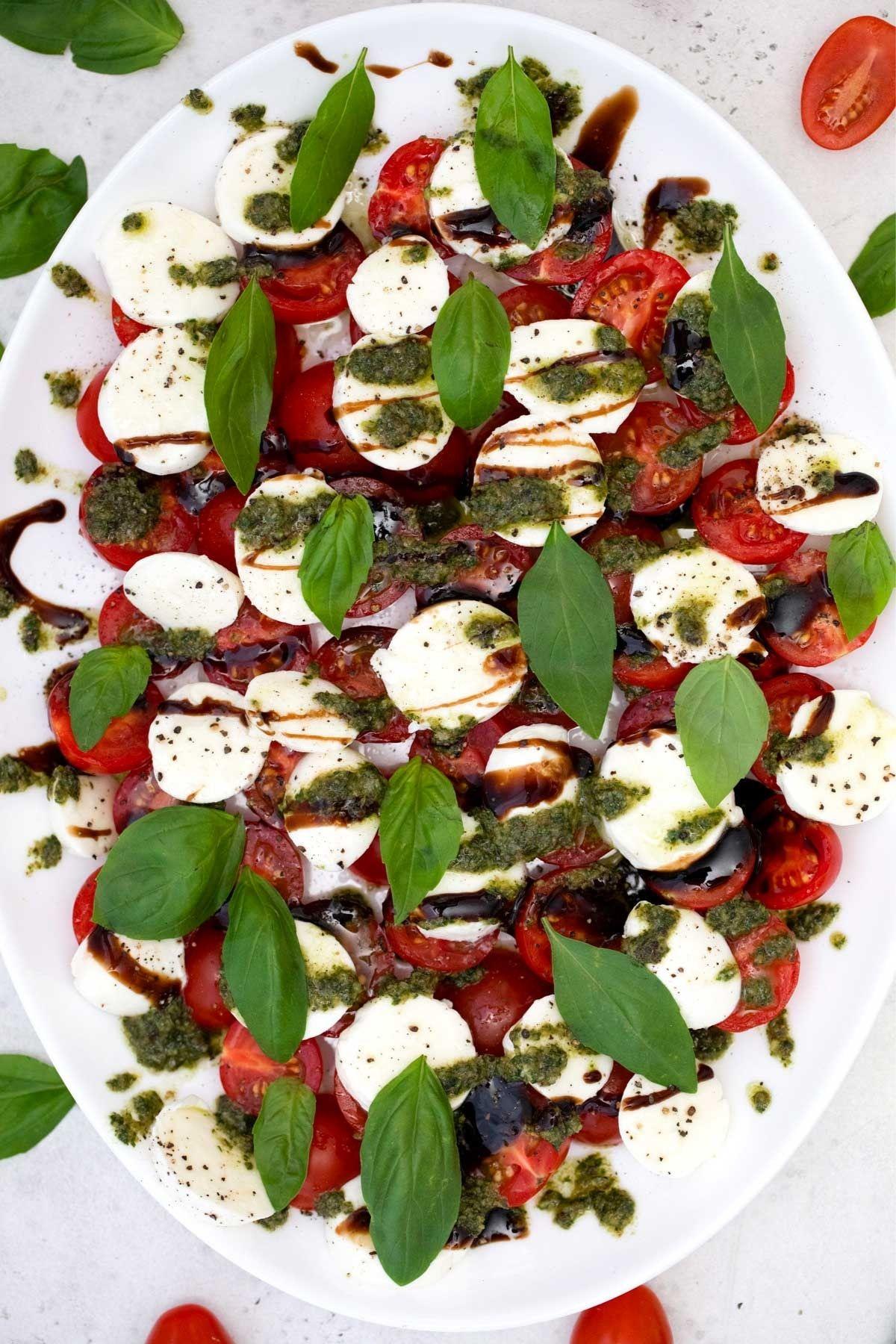 Caprese salad displayed on white serving platter