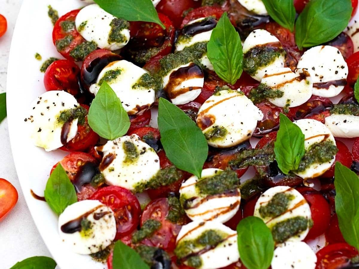 White platter with tomato cheese and basil salad