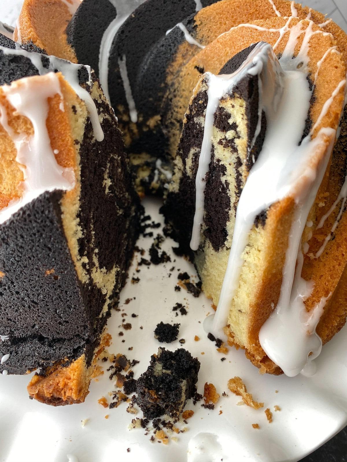 Slice out of sGlazed swirl bundt cake on standwirl bundt cake on stand