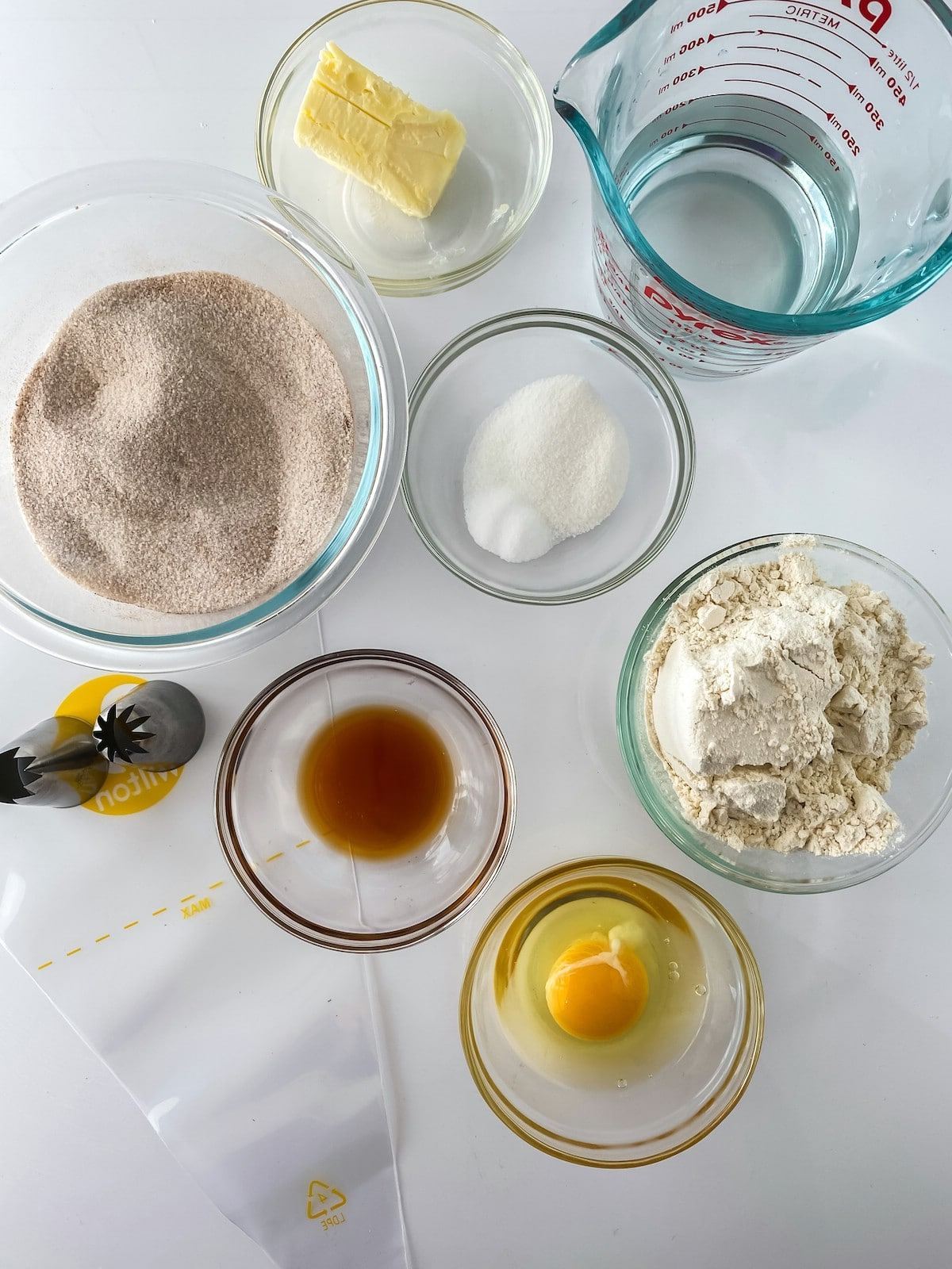 Ingredients for churros in glass bowls on table