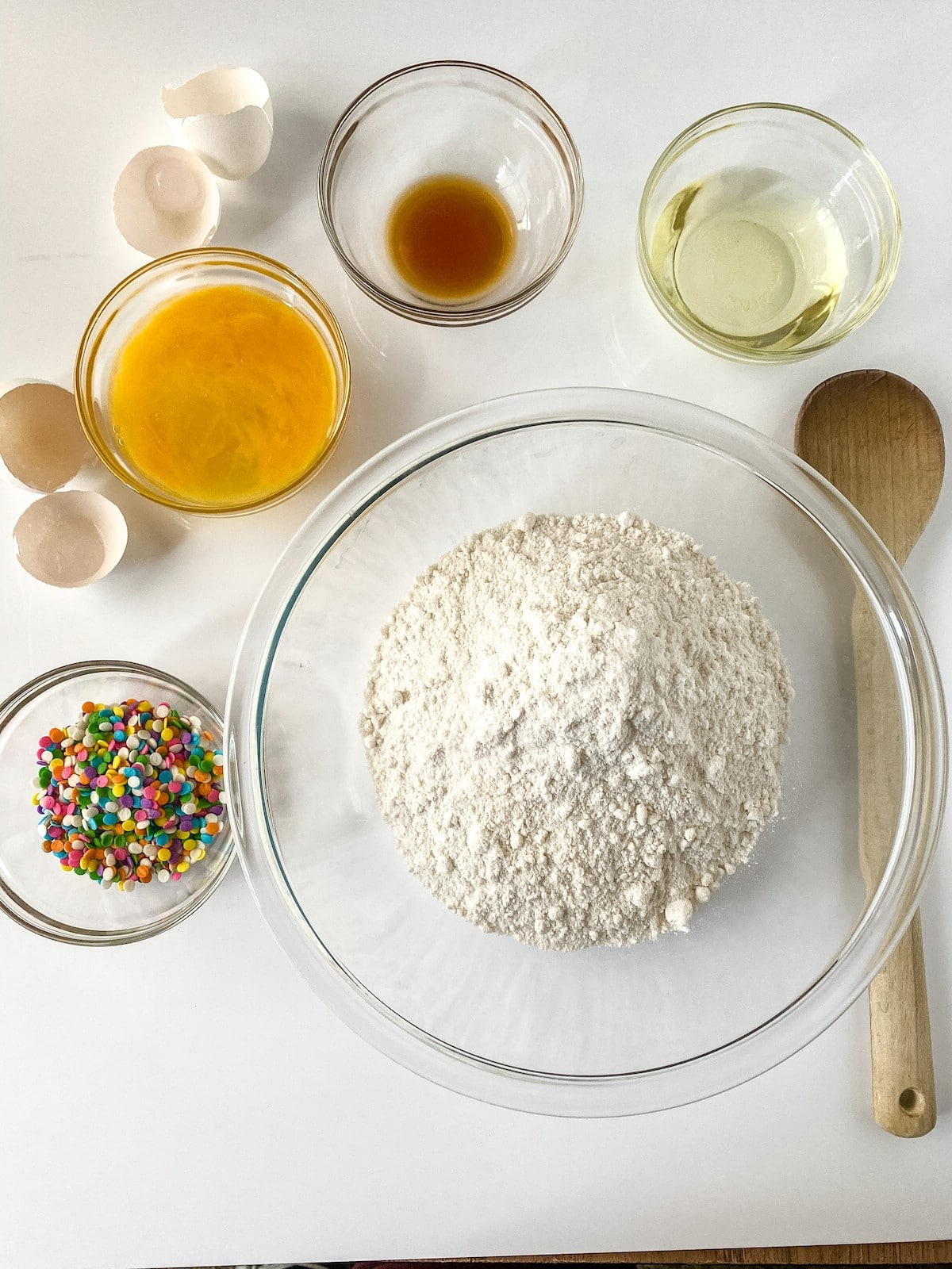 Ingredients for confetti sandwich cookies in bowls on table
