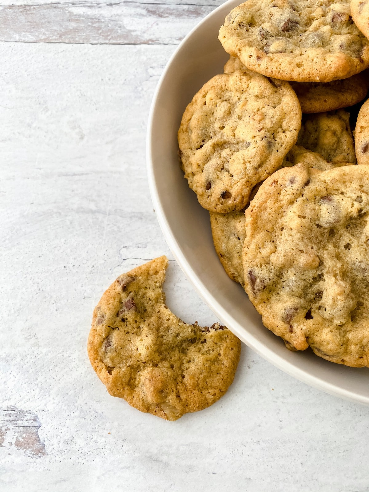 Cookie with bite out on marble by bowl of cookies