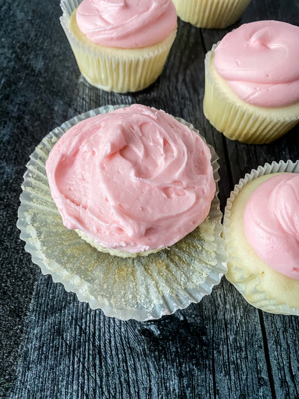 Cupcakes with pink icing on wood