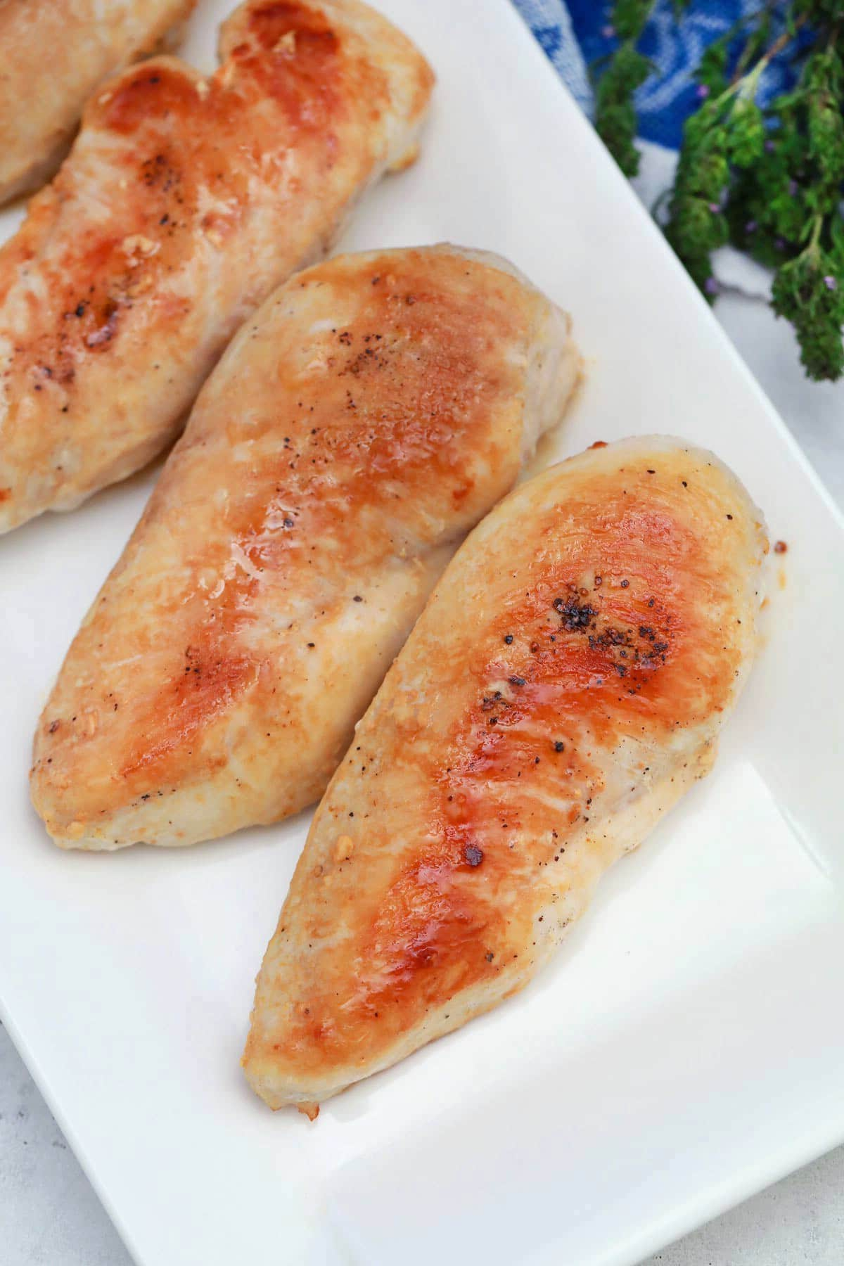 Cooked chicken breasts laying on white platter