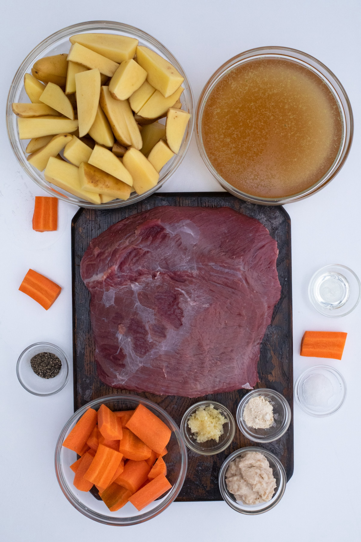 Ingredients for beef roast on white table in bowls