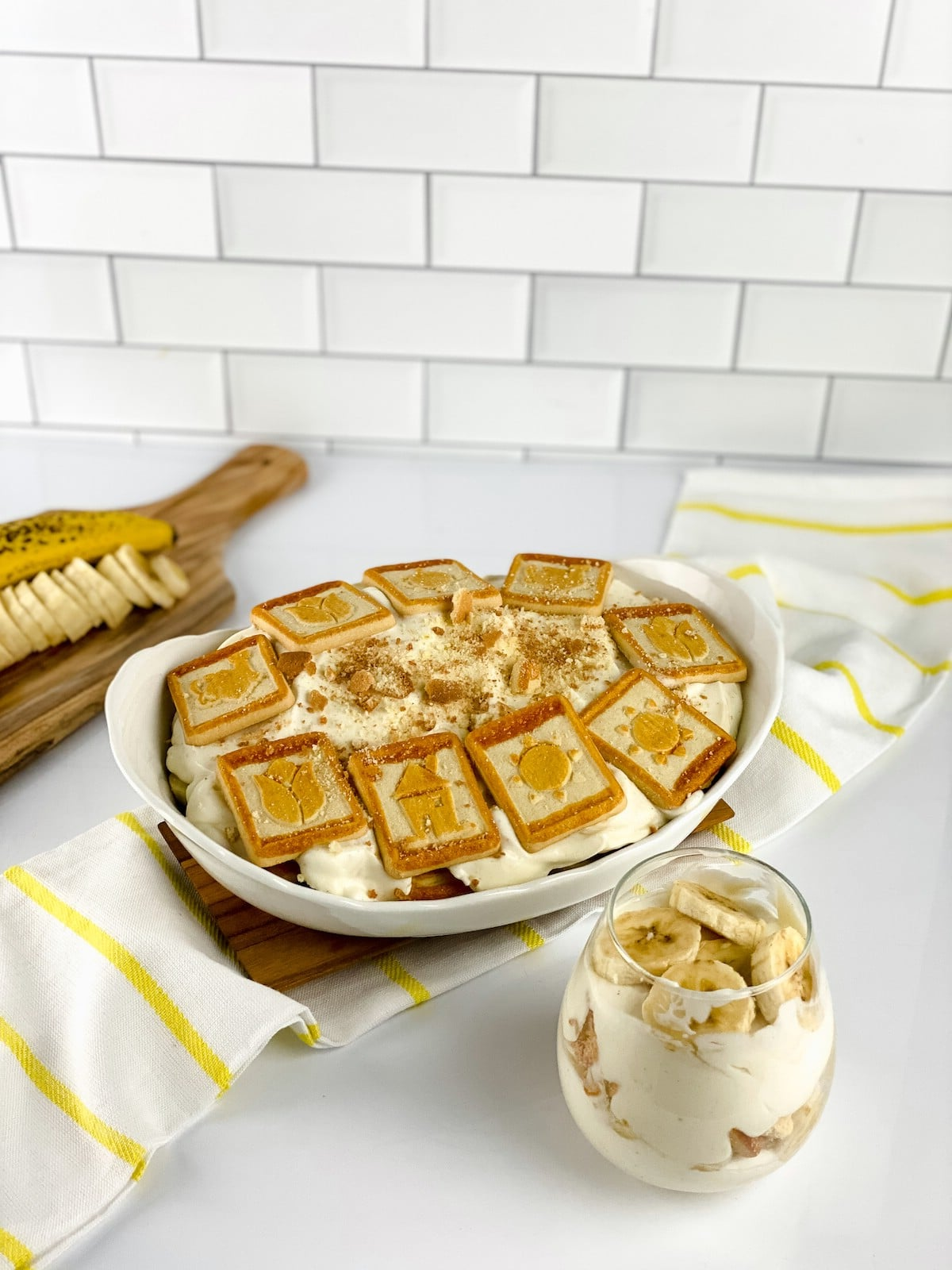 Individual servings of banana pudding in glasses by large bowl