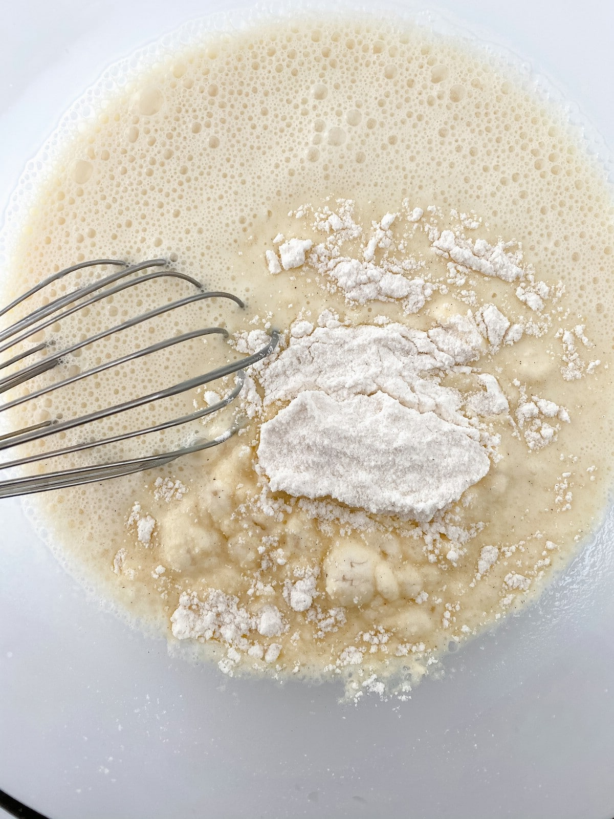 Whisking pudding mix into milk mixture in glass bowl
