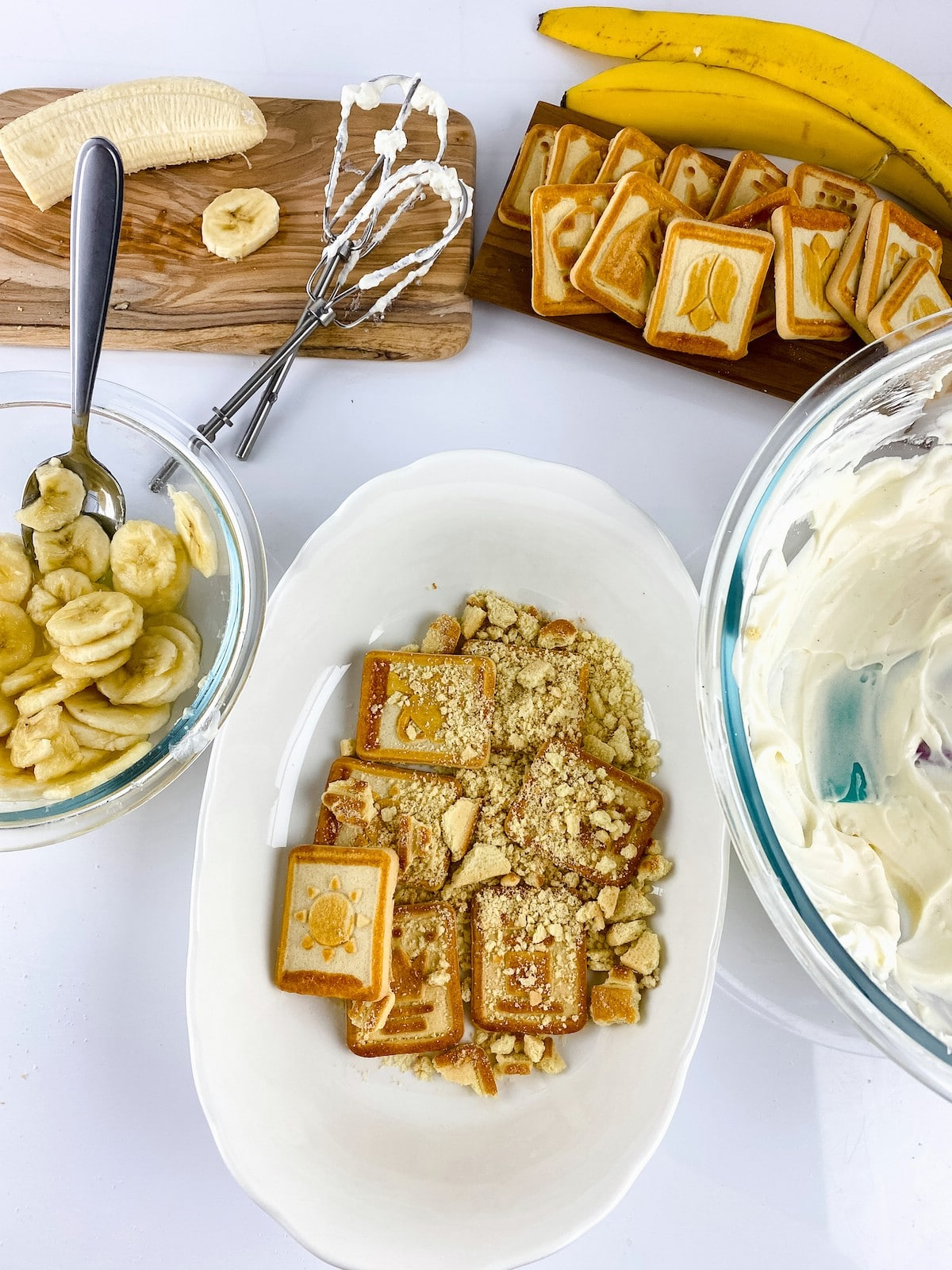 Assembling banana pudding layers in white bowl