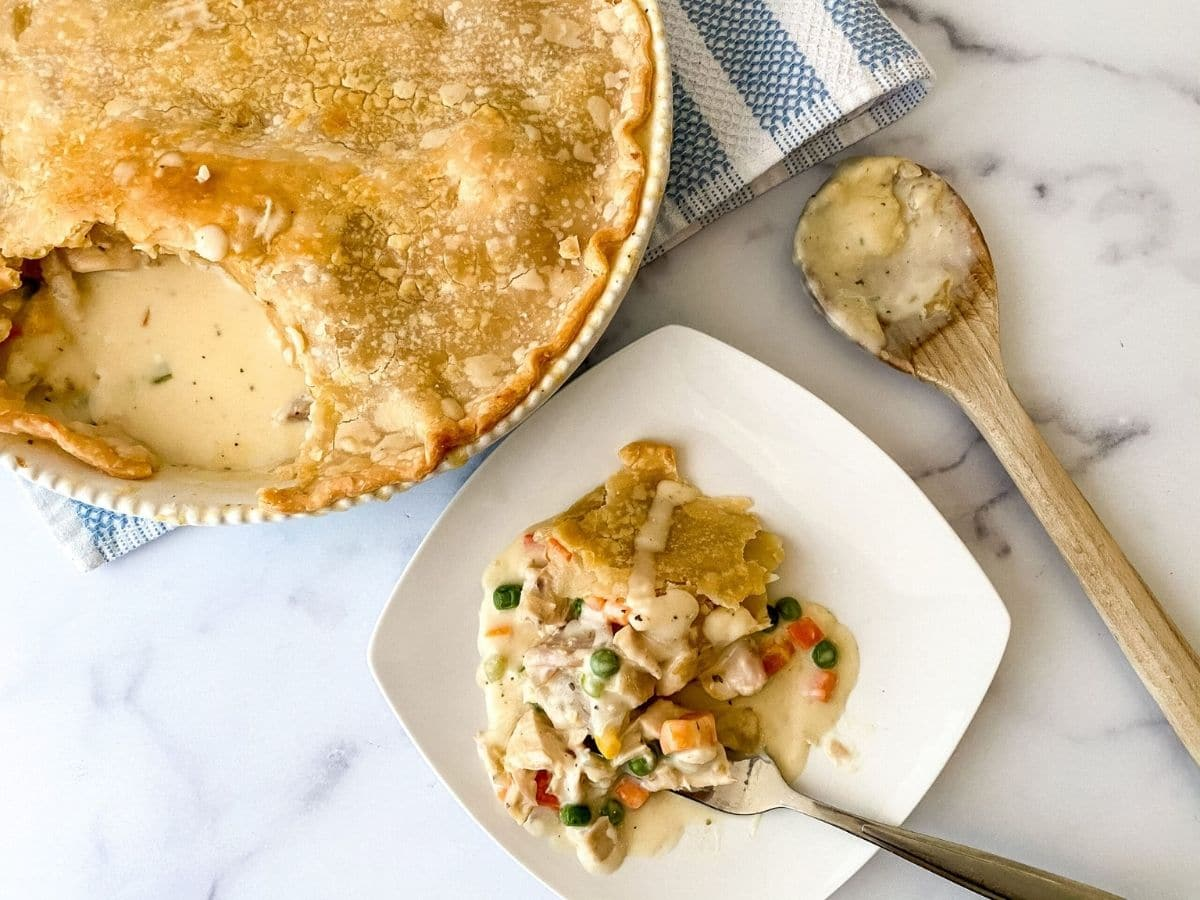 Chicken pot pie baked on blue and white striped towel next to white plate with serving