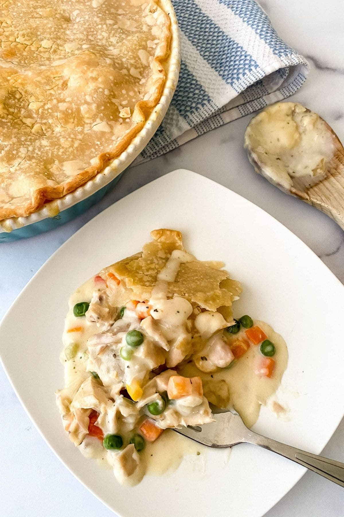 Square white plate next to round dish with pot pie and spoon