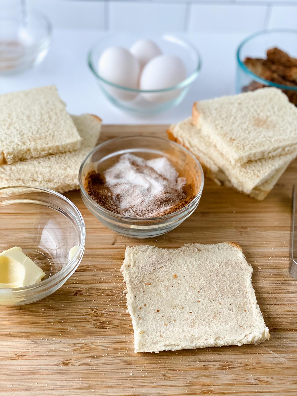 Adding cinnamon sugar to bread
